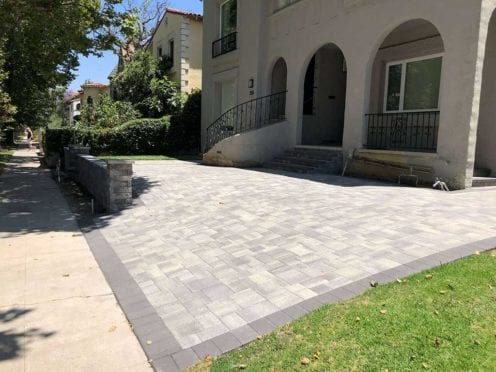 Gray Charcoal Driveway with Stone Wall